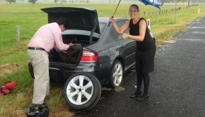 Realtors Maddy Richie and Terry Deefholts changing a flat tyre in wild weather - Elders Real Estate Grafton